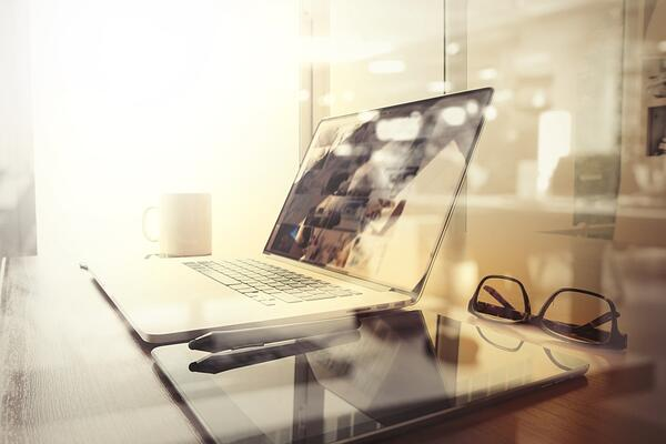 Office workplace with laptop and smart phone on wood table and london city blurred background